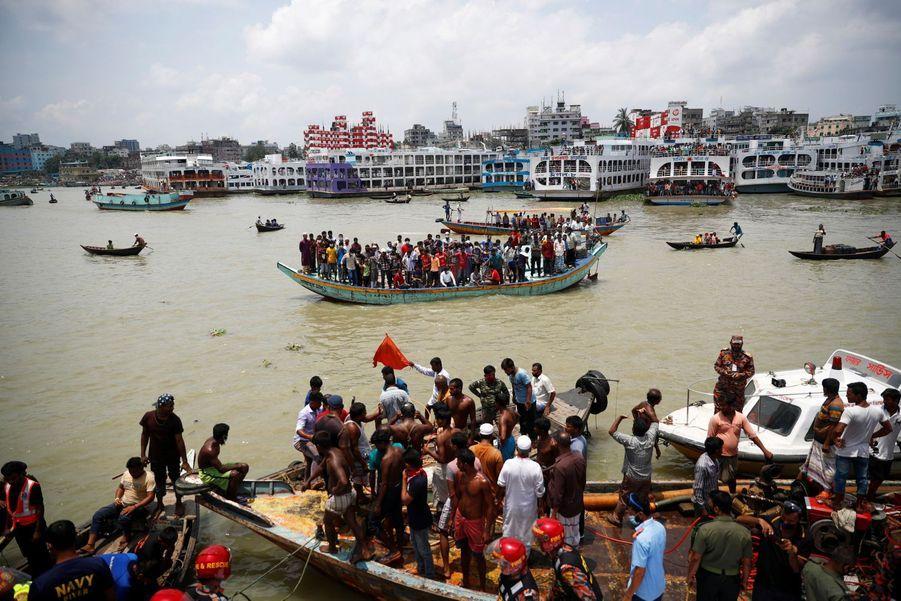 Des badauds regardent le lieu du naufrage depuis une embarcation sur le fleuve deBuriganga à Dacca.