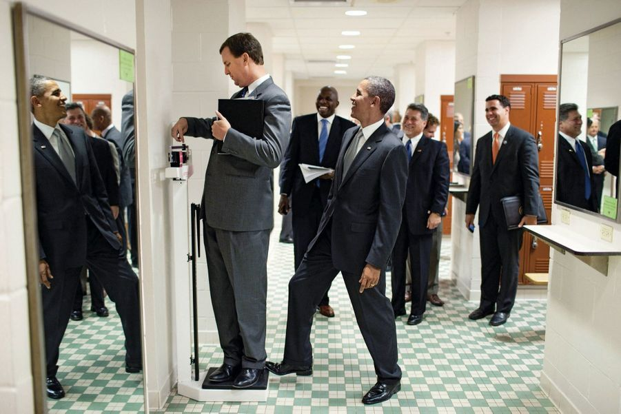 Taquin, Barack Obama appuie sur la balance où se pèse Marvin Nicholson, responsable de ses voyages, au Texas, en août 2010.