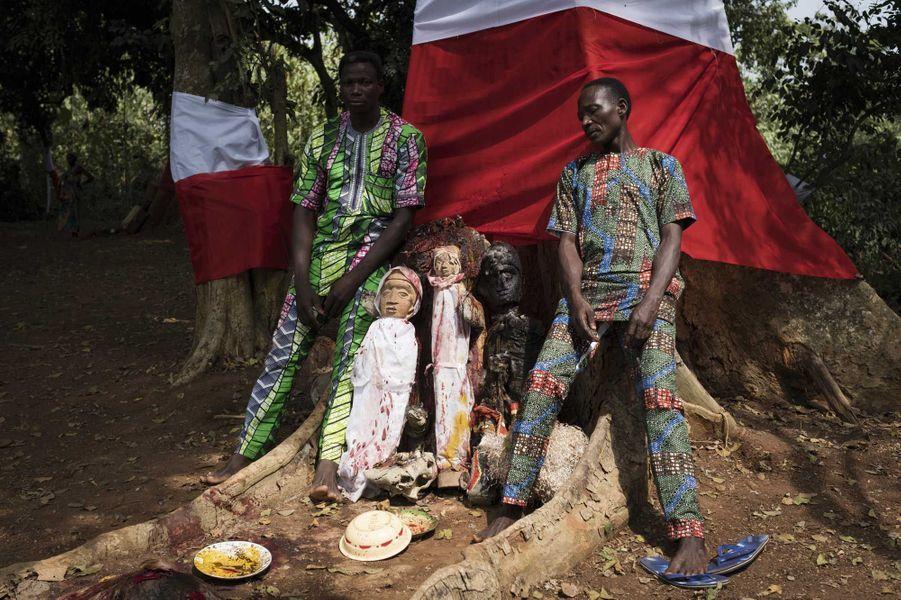 Après avoir accompli un sacrifice, ces deux hommes entourent le fétiche des jumeaux devant un arbre sacré.