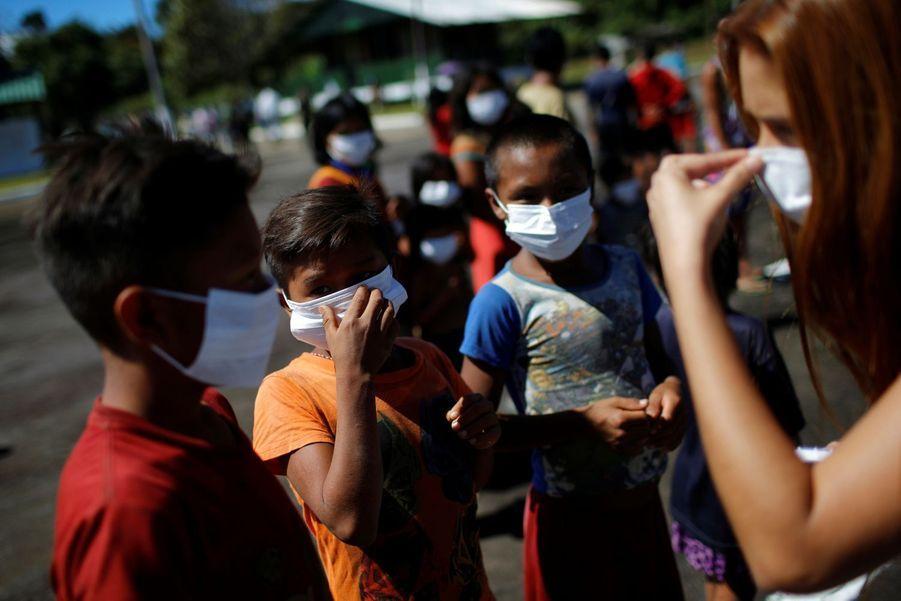 Une infirmière montre aux jeunes yanomamis comment porter un masque.