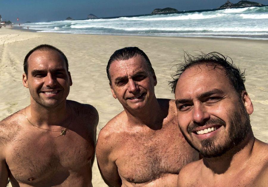 Août 2018. Au pied de sa maison sur la plage, dans le quartier de Barra à Rio, avec deux de ses fils. Eduardo (à g.), député fédéral de São Paulo depuis 2015, et Carlos (à dr.), conseiller municipal de Rio, élu à 17 ans.