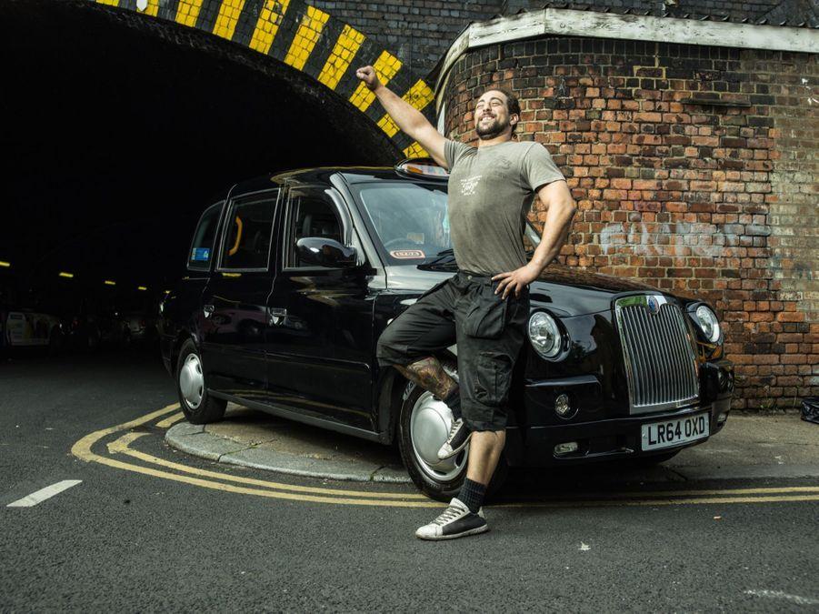 Ce mécanicien dans un garage de réparation de taxis pose devant son entreprise à Bethnal Green, à Londres.