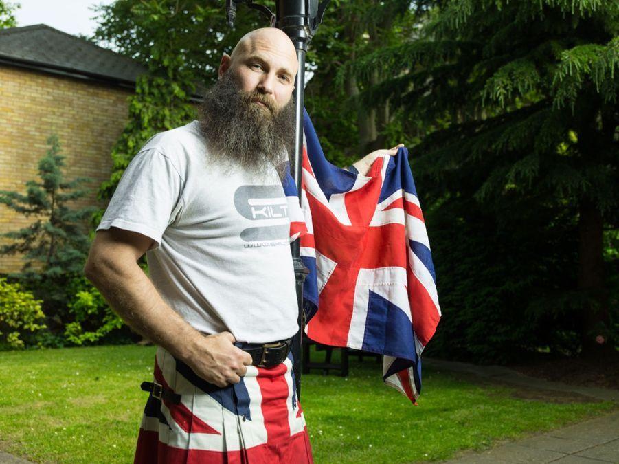 """""""Comment tolérer les gens qui ne nous tolèrent pas ?"""" demande--t-ol. Il pose dans son jardin à Bethnal Green en brandissant l'Union Jack."""