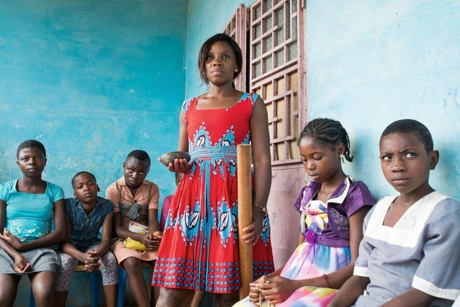 Michèle Bassa Ebassi, une jeune tantine de Bafia, présente certains des instruments utilisés : la pierre à écraser, employées en cuisine, et le pilon