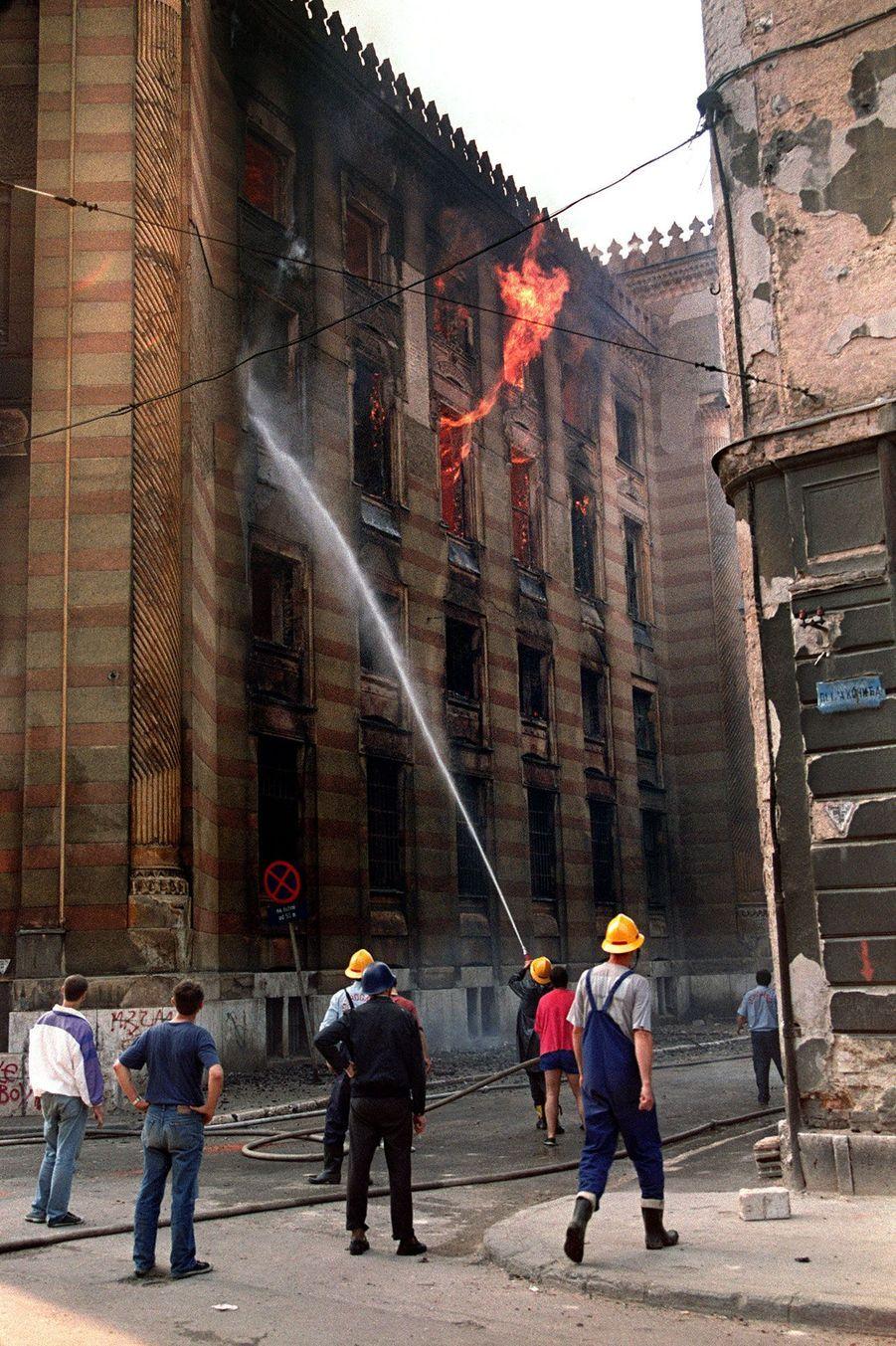 Des pompiers éteignent le feu de la bibliothèque de Sarajevo, le 26 août 1992.