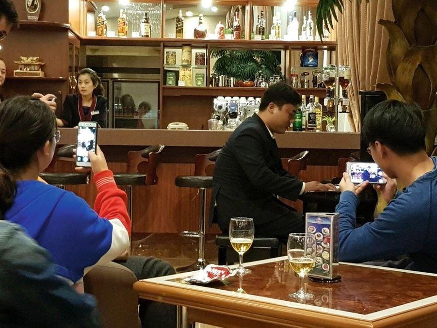 Scène de la vie quotidienne au bar de l'hôtel Koryo. Un jeune client coréen s'est installé au piano et joue spontanément devant des touristes chinois qui immortalisent la scène sur leur Smartphone.
