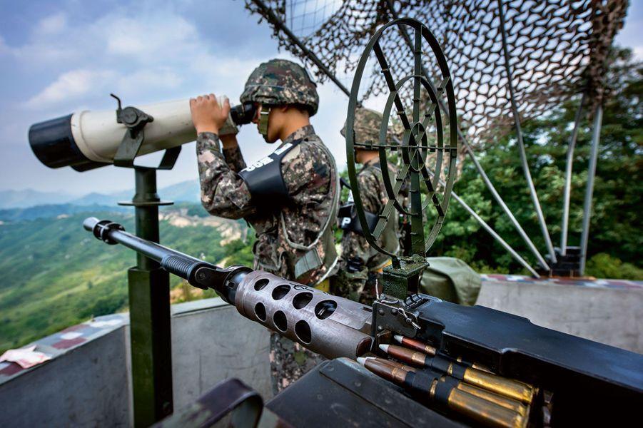 Armés d'une mitrailleuse lourde, des Sud-Coréens surveillent la zone depuis un édifice antichar.