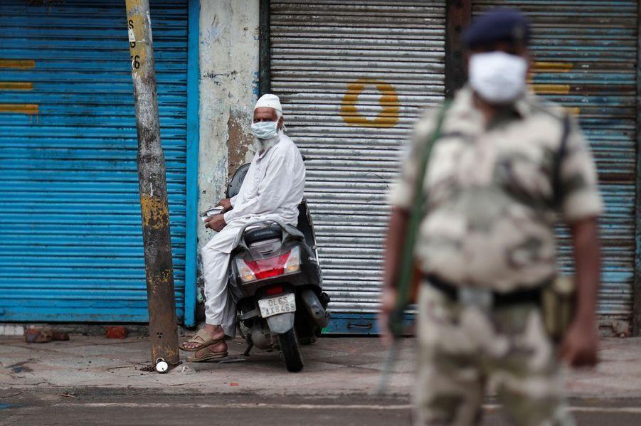 Un homme musulman porte un masque à l'entrée de Jama Masjid, une mosquée, pendant l'Aïd, près d'un soldat dans les vieux quartiers de Delhi.