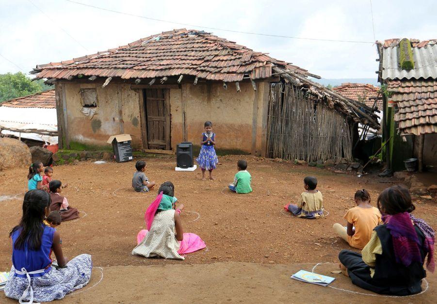 Des enfants qui n'ont pas pu assister à leur cours en ligne faute de connexion internet sont assis sur le sol à distance les uns des autres. Ils écoutent des leçons pré-enregistrées sur des hauts-parleurs dans l'état deMaharashtra, à l'ouest du pays.