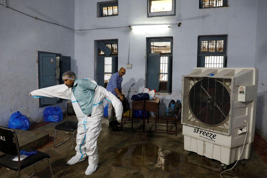 Un homme s'équipe avant de pratiquer des tests dans cette école de New Delhi devenue centre de tests.
