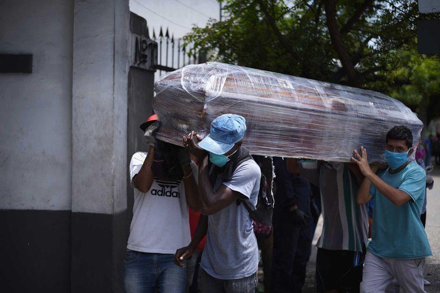 Des hommes transportent uncercueil, àGuayaquil, le 11 avril