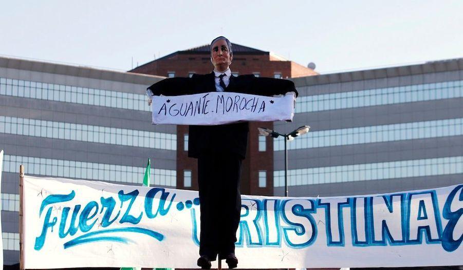 """Une figurine de Nestor Kirchner tient une pancarte """"Accroche-toi, Brunette""""."""
