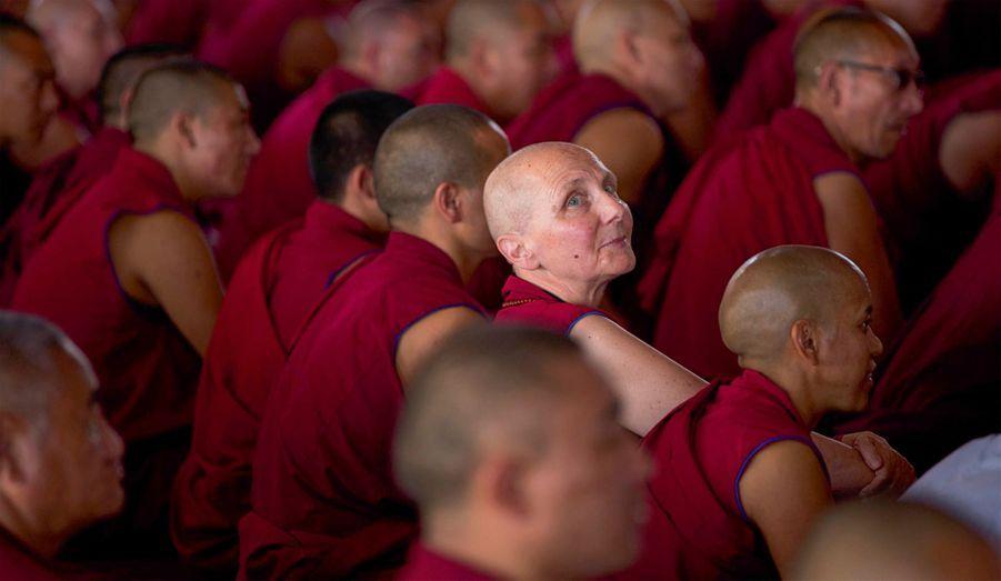 Le regard inspiré, une nonne occidentale au crâne rasé perdue parmi une marée de moines. Les femmes demeurent minoritaires parmi les officiants.
