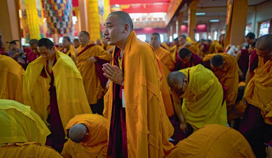 Les moines se prosternent devant le trône au moment où le dalaï-lama s'y installe.