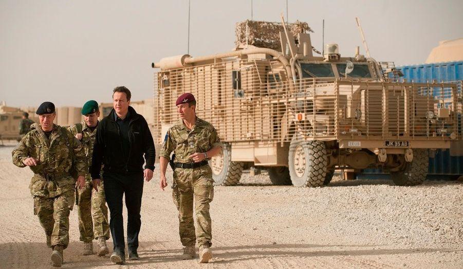 David Cameron marche avec ses troupes. Au loin un véhicule blindé sur la base de patrouille entre Lashkar Gah et Geresh.