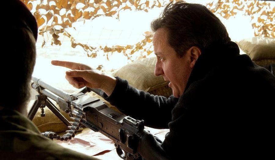 Caché en haut du point d'observation de sangar, David Cameron espionne un village voisin.