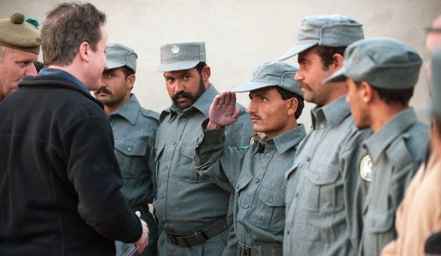 Un soldat des patrouilles afghanes salue le Premier ministre britannique alors qu'il passe au centre de formation de la police de Helmand, près de Lashkar Gah en Afghanistan.