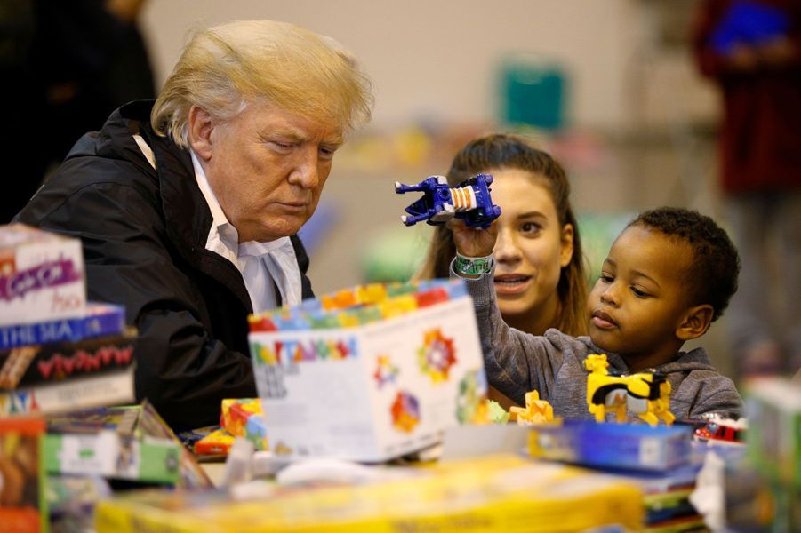 Donald Trump découvre les jouets d'un enfant dans un centre pour rescapés de Houston, samedi.
