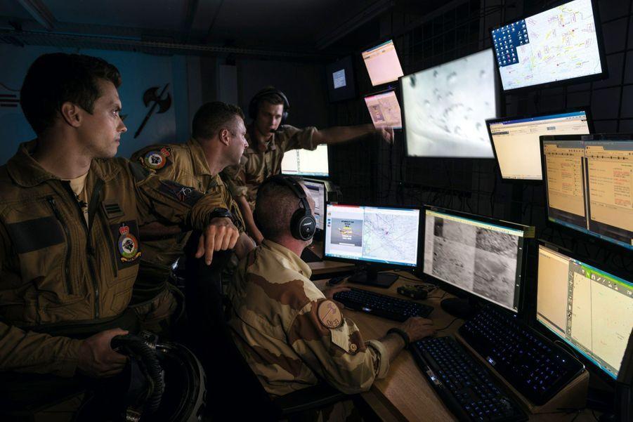 Dans la « tranche arrière », l'opérateur image et le coordinateur tactique briefent l'équipage d'un Mirage 2000 D avant une frappe.