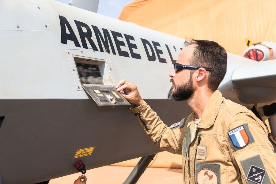 Inspection de routine. Comme tout pilote, et même s'il ne quittera pas la base de Niamey (Niger), Sébastien fait le tour de son appareil avant le décollage. Ici, il contrôle les « trappes de connexion ».
