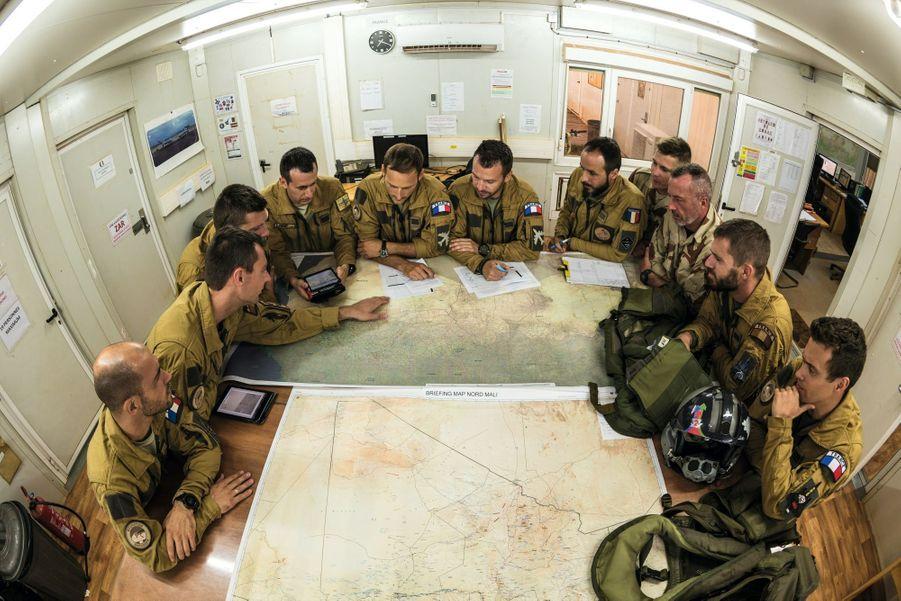 Briefing avant mission devant les cartes de la région. Contrairement aux Américains, les Français ne dirigent pas leurs drones depuis le sol national. Ils travaillent sur place, directement avec les équipages des transporteurs, des ravitailleurs et les pilotes de chasse (à dr., avec le casque).