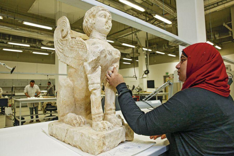 Dans le laboratoire de conservation des pierres, Amira Abd El-Hakim nettoie un sphinx: ses 360 morceaux ont été mal assemblés lors d'une précédente restauration.