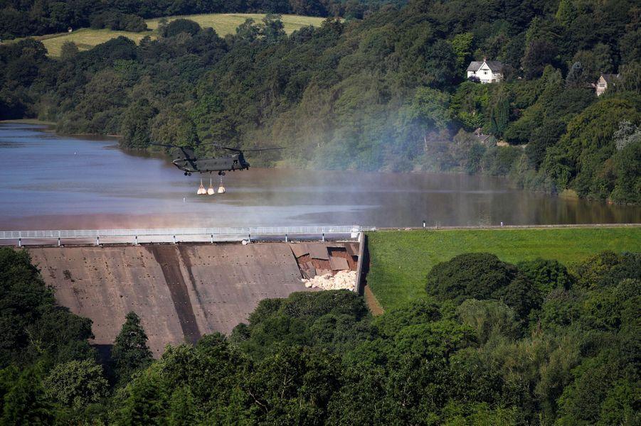 Un hélicoptère Chinook dépose des sacs de sable sur la partie endommagée du barrage de Whaley Bridge, vendredi.
