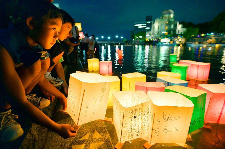 Des enfants déposent des lanternes de papiers dans la rivière Motoyasu en souvenir des victimes