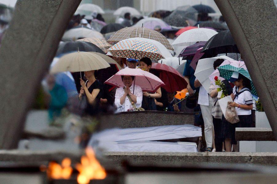 Des gens priant devant le Memorial de la paix