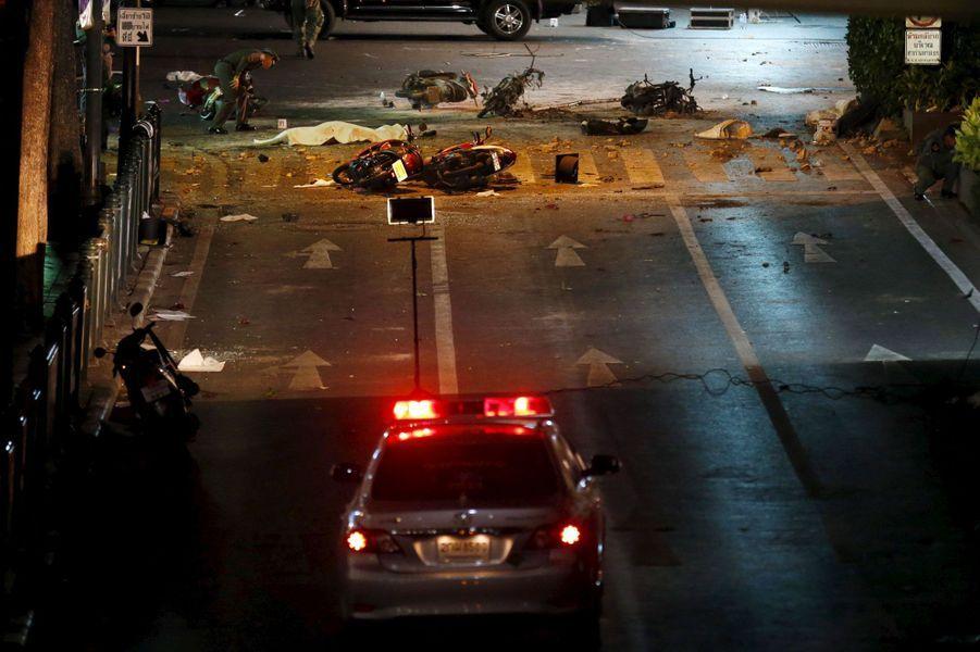 """La police recherchait mardi un """"suspect"""" identifié grâce aux images de vidéo-surveillance après """"la pire attaque jamais"""" commise en Thaïlande d'après le chef de la junte au pouvoir, et qui a fait au moins 21 morts à Bangkok. Les enquêteurs étaient à pied d'oeuvre sur les lieux de l'attentat à la bombe qui a frappé lundi en pleine heure de pointe un sanctuaire du centre de Bangkok, très fréquenté, y compris par les touristes étrangers. D'après le chef de la junte et Premier ministre, Prayut Chan-O-Cha, la police est à la recherche d'un suspect apparaissant sur les images des caméras de surveillance, """"originaire du nord-est du pays et membre d'un groupe opposé à la junte"""".Le nord-est de la Thaïlande, la région de l'Issan, est le bastion des Chemises rouges, qui soutiennent l'ancien gouvernement chassé du pouvoir après des mois de manifestations suivies par un coup d'Etat militaire en 2014. """"La bombe visait à tuer autant de personnes que possible, puisque le sanctuaire est bondé aux alentours de 06 et 07H00 le soir"""", a déploré mardi matin le porte-parole de la police Prawut Thavornsiri. """"Le bilan est maintenant de 21 tués et 123 blessés. 14 des personnes décédées sont mortes sur le site de l'explosion"""", a-t-il ajouté précisant que la bombe contenait probablement trois kilos d'explosifs."""