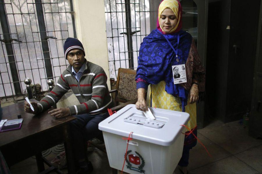 A Dhaka, cette femme vote sous le regard d'un officier.