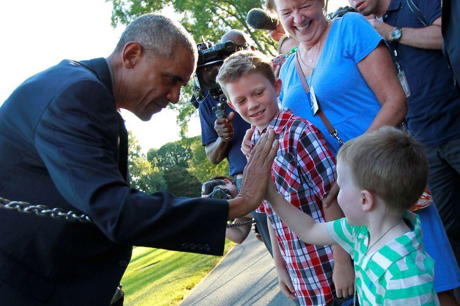 Barack Obama tape dans la main d'un enfant à la Maison Blanche, le 23 août 2016.