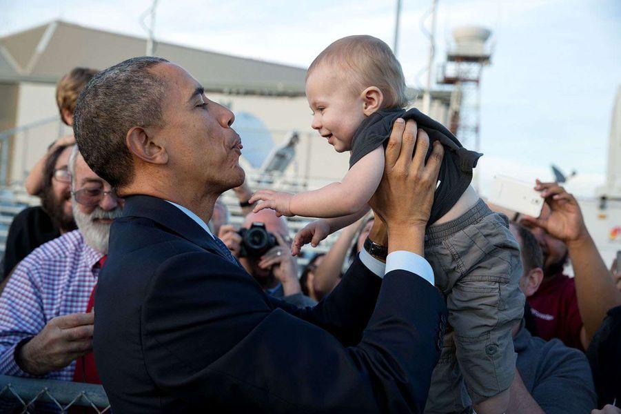 Barack Obama porte un bébé à son arrivée à l'aéroport de San Francisco (Californie), le 12 février 2015.