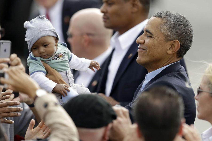 Barack Obama porte un bébé à son départ de l'aéroport de San Francisco (Californie), le 10 octobre 2015.