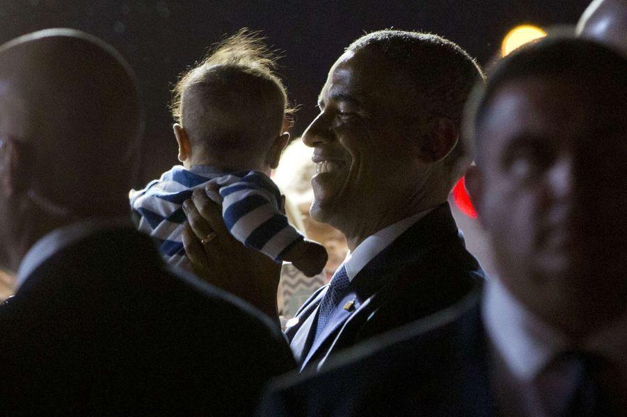 Barack Obama prend dans ses bras un bébé sur le tarmac de l'aéroport de Phoenix (Arizona), le 7 janvier 2015.