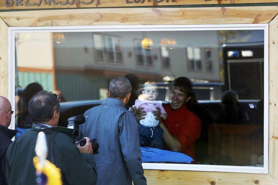 Barack Obama salue le bébé d'un commerçant de Seward (Alaska), le 1er septembre 2015.