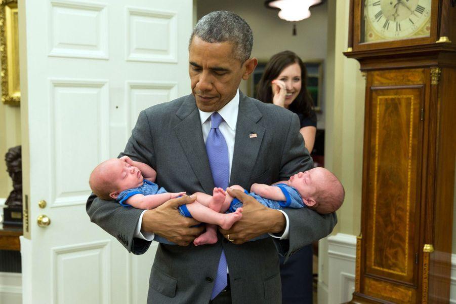 Barack Obama tient dans ses bras les jumeaux de Katie Beirne Fallon, la directrice des Affaires législatives, à la Maison-Blanche, le 17 juin 2015.