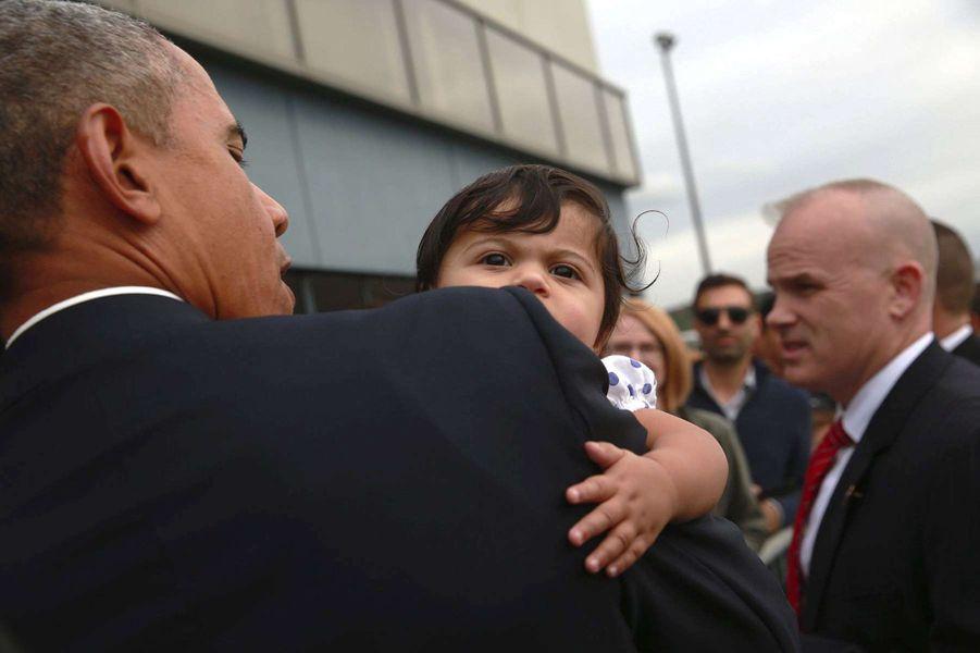Barack Obama tient dans ses bras une fillette à l'aéroport de Seattle (Washington), le 9 octobre 2015.