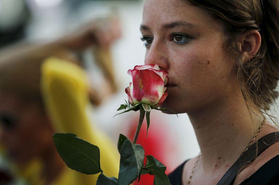 Une jeune femme partage le deuil, une rose à la main