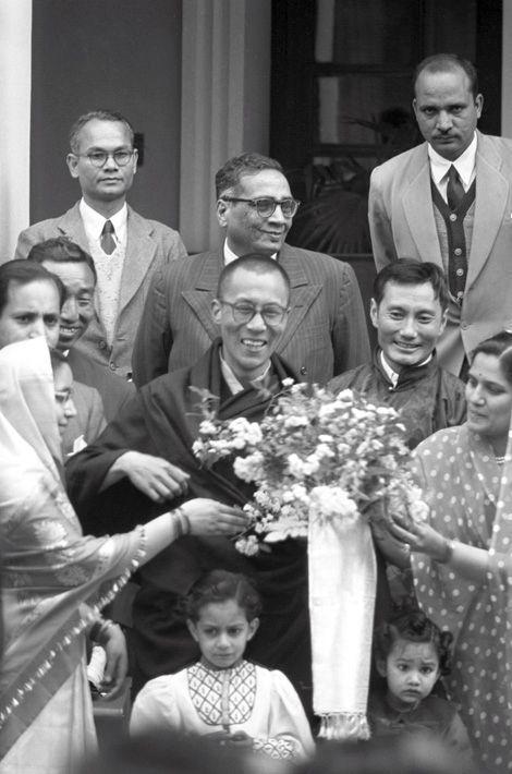 Traqué par les Chinois, le 14e DALAI-LAMA (23 ans) a fui le Tibet et trouvé refuge en Inde. Mussoorie (Uttar Pradesh), 20 avril 1959 : plan souriant de face du Dalai-Lama, avec à sa gauche Gyalo THONDUP, un de ses frères aînés, posant entouré par le comité d'accueil. Après avoir traversé la région des territoires de la North East Frontier Agency (NEFA) qui sépare l'Inde du Tibet et de la Chine, le Dalai-Lama a pris le train à Tezpur en Assam pour se rendre dans sa nouvelle résidence de Birla House, à Mussoorie, où lui et ses partisans sont très attendus.