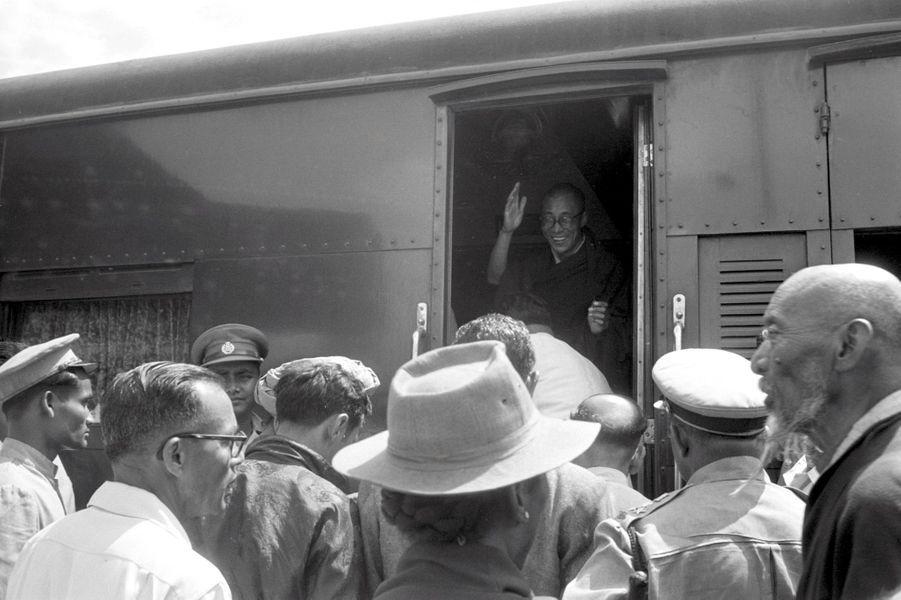 Traqué par les Chinois, le 14e DALAI-LAMA (23 ans) a fui le Tibet et trouvé refuge en Inde. Tezpur, 18 avril 1959 : ici, dans un compartiment du train qui lui est réservé, le Dalai-Lama sourit et salue la foule venue assister à son départ. A chaque gare, des fidèles l'attendent tout le long de son parcours qui durera près de trois jours. Après avoir traversé la région des territoires de la North East Frontier Agency (NEFA) qui sépare l'Inde du Tibet et de la Chine, le Dalai-Lama a fait son entrée dans la ville de Tezpur en Assam, où lui et ses partisans étaient attendus par la presse internationale. De là, il doit prendre le train spécial envoyé par le Pandit Nehru (1er ministre indien) pour atteindre sa résidence définitive, à Mussoorie (Uttar Pradesh).
