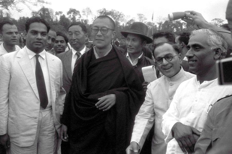 Traqué par les Chinois, le 14e DALAI-LAMA (23 ans) a fui le Tibet et trouvé refuge en Inde : 18 avril 1959 : son arrivée à la frontière de l'Assam, après avoir traversé la région des territoires de la North East Frontier Agency (NEFA) qui sépare l'Inde du Tibet et de la Chine. Avant de rejoindre la ville de Tezpur où lui et ses partisans sont attendus par la presse internationale, le Dalai-Lama fait quelques pas pour saluer le comité d'accueil venu l'attendre à la frontière. A sa gauche, le représentant indien de Nehru, R. V. MENON, et derrière, coiffé de son chapeau, Gyalo THONDUP, un des frères aînés du Dalai-Lama.