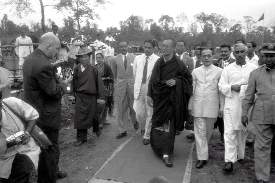 Traqué par les Chinois, le 14e DALAI-LAMA (23 ans) a fui le Tibet et trouvé refuge en Inde : 18 avril 1959 : son arrivée à la frontière de l'Assam, après avoir traversé la région des territoires de la North East Frontier Agency (NEFA) qui sépare l'Inde du Tibet et de la Chine. Avant de rejoindre la ville de Tezpur où lui et ses partisans sont attendus par la presse internationale, le Dalai-Lama fait quelques pas pour saluer le comité d'accueil venu l'attendre à la frontière. A sa gauche, le représentant indien du Pandit Nehru, R. V. MENON.