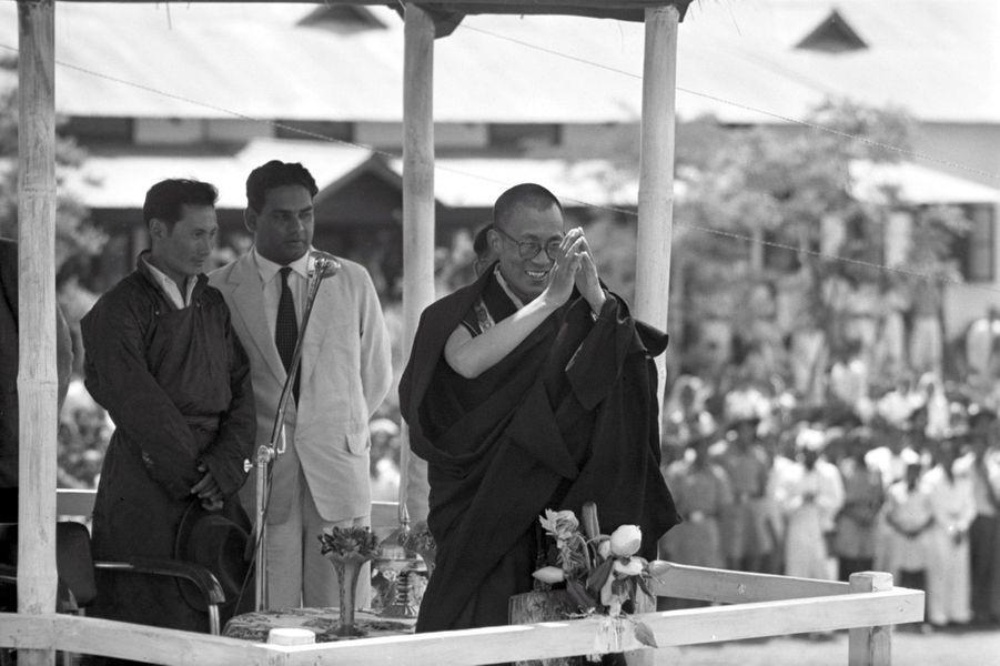 """Traqué par les Chinois, le 14e DALAI-LAMA (23 ans) a fui le Tibet et trouvé refuge en Inde. Après avoir traversé la région des territoires de la North East Frontier Agency (NEFA) qui sépare l'Inde du Tibet et de la Chine, le Dalai-Lama à fait son entrée dans la ville de Tezpur en Assam, où lui et ses partisans sont attendus par la presse internationale. De là, il devra prendre le train spécial envoyé par le Pandit Nehru (1er ministre indien) pour atteindre sa résidence définitive, à Mussoorie. Tezpur, 18 avril 1959 : sous un toit de chaume tibétain, le Dalai-Lama salue la foule des fidèles qui se sont rassemblés pour écouter et recevoir la bénédiction du """"Bouddha vivant"""". En arrière-plan à gauche, Gyalo THONDUP, un des frères aînés du Dalai-Lama."""