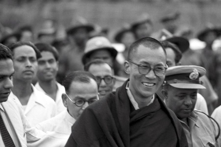 Traqué par les Chinois, le 14e DALAI-LAMA (23 ans) a fui le Tibet et trouvé refuge en Inde : 18 avril 1959 : son arrivée à la frontière de l'Assam, après avoir traversé la région des territoires de la North East Frontier Agency (NEFA) qui sépare l'Inde du Tibet et de la Chine. Avant de rejoindre la ville de Tezpur où lui et ses partisans sont attendus par la presse internationale, le Dalai-Lama fait quelques pas pour saluer le comité d'accueil venu l'attendre à la frontière.