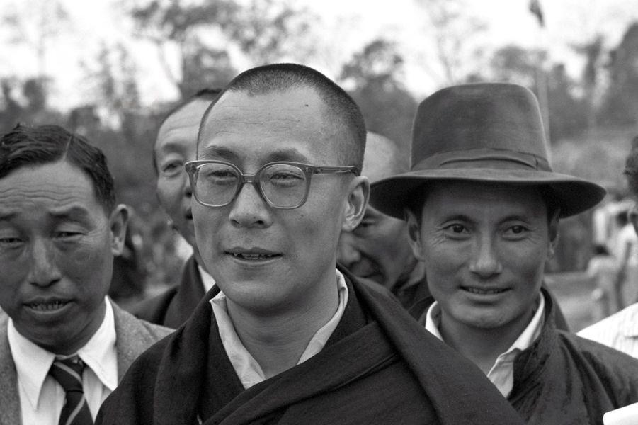 Traqué par les Chinois, le 14e DALAI-LAMA (23 ans) a fui le Tibet et trouvé refuge en Inde : 18 avril 1959 : son arrivée à la frontière de l'Assam, après avoir traversé la région des territoires de la North East Frontier Agency (NEFA) qui sépare l'Inde du Tibet et de la Chine. Avant de rejoindre la ville de Tezpur où lui et ses partisans sont attendus par la presse internationale, le Dalai-Lama descend d'une vieille conduite intérieure grise de l'armée indienne pour faire quelques pas et saluer les nombreuses personnes venues l'accueillir, dont le représentant indien de Nehru, R. V. MENON, et derrière, coiffé de son chapeau, Gyalo THONDUP, un des frères aînés du Dalai-Lama.