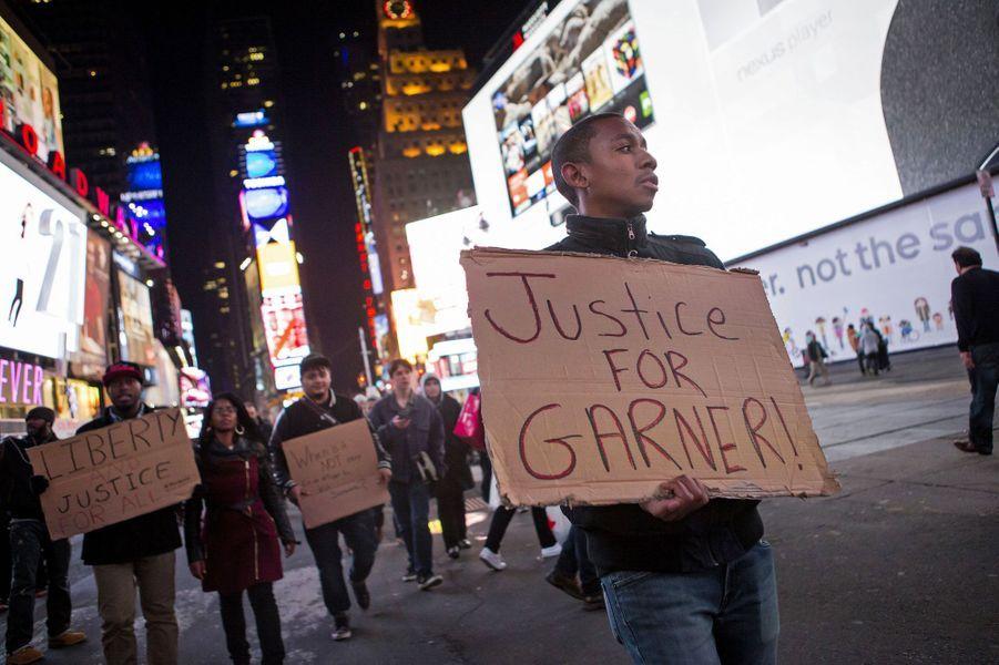 """Des milliers de manifestants se sont rassemblés mercredi soir dans plusieurs quartiers de New York, et une trentaine de personnes ont été arrêtées, après la décision d'un grand jury de ne pas inculper un policier blanc impliqué dans la mort d'un père de famille noir. Cette décision est intervenue dix jours après une décision similaire à Ferguson (Missouri) qui avait suscité des émeutes, et de très importantes forces de police avaient été déployées à New York pour éviter tout incident.Le ministre de la Justice Eric Holder a par ailleurs immédiatement annoncé mercredi soir une enquête fédérale sur une éventuelle violation des droits civiques de la victime, Eric Garner. Plusieurs cortèges ont convergé vers Broadway et Times Square, où quelque 5.000 personnes étaient rassemblées en fin de soirée, selon le Washington Post. Des conducteurs bloqués par les manifestations klaxonnaient en signe de soutien, selon le journal.Les manifestants scandaient """"Pas de justice, pas de paix"""", un slogan de ralliement des manifestations de Ferguson, ou portaient des panneaux """"Ferguson est partout"""", """"la brutalité de la police et les meurtres doivent s'arrêter"""", ou encore """"la vie des Noirs compte"""". Plusieurs centaines de manifestants se sont rassemblés près du Rockefeller Center et certains ont été arrêtés alors qu'ils essayaient de s'asseoir sur la chaussée, a constaté l'AFP.C.R. avec AFP"""