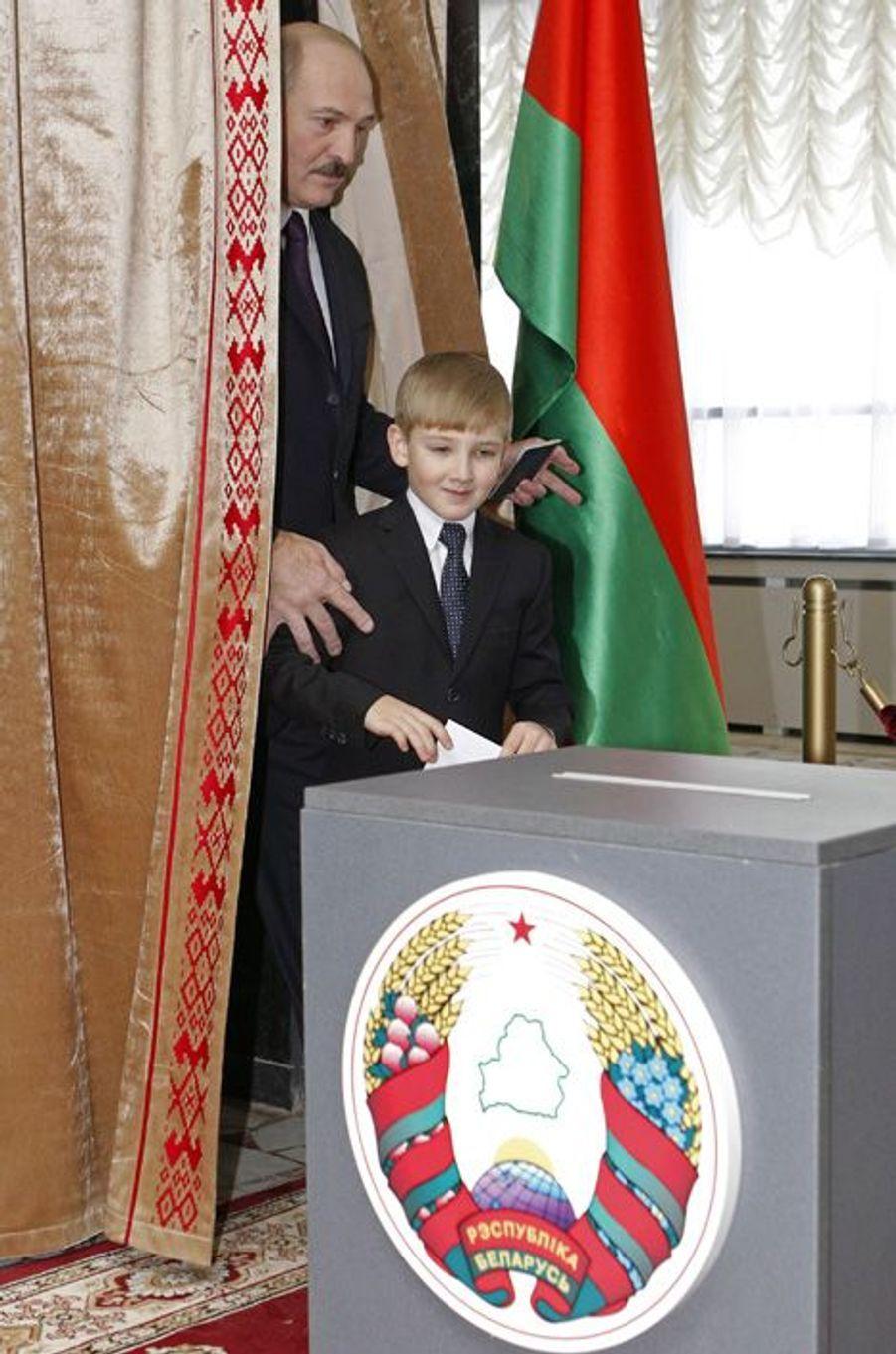 Alexandre Loukachenko vote avec son fils Nikolaï à Minsk, le 19 décembre 2010