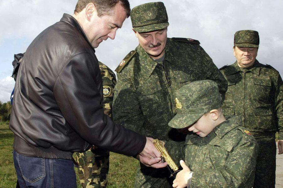 Dmitri Medvedev offre à Nikolaï, le fils d'Alexandre Loukachenko, un pistolet en or, le 29 septembre 2009