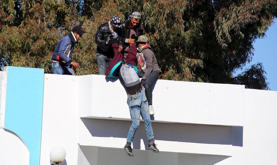 Des Tunisiens rattrapant un homme qui aurait tenté de se suicider jeudi à Kasserine